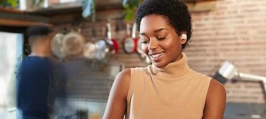 Woman in a kitchen wearing WF-1000XM4 headphones