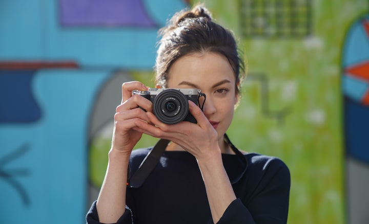 Portrait of woman taking photos outdoors