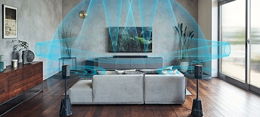 SA-RS3S rear speakers on pedestals in a living room with a sofa, soundbar on a cabinet and large-screen TV. Sound waves are emanating from the speakers to the ceiling and bouncing off the walls.