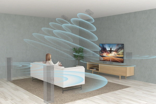 A woman watching TV on a sofa in a living room with sound waves coming from virtual speakers above, behind and in front of her