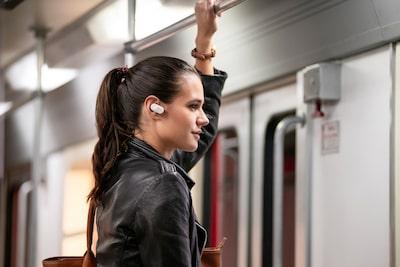 Lifestyle shot of man listening to WF-1000XM3 headphones on public transport