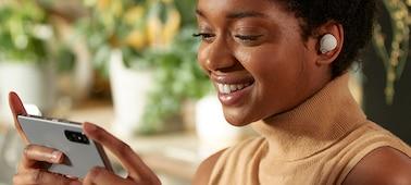 Woman wearing WF-1000XM4 headphones, watching content on her smartphone